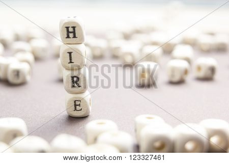 HIRE word written on wood block. Wooden Abc.