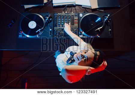 Cute dj woman having fun playing music on vinyl record deck at club party nightlife lifestyle. Top view