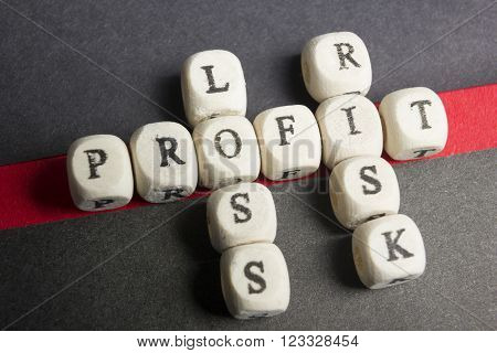 Profit, loss and risk crossword blocks on table. Top view.