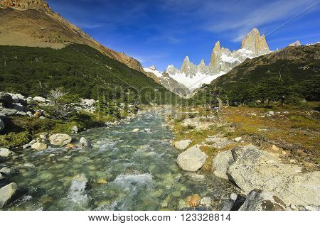 flowing river in forest near mountain Fitz Roy with glaciers in Argentina Patagonia with blue sky