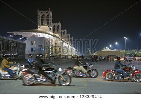 Central Desertic Area, Bahrain - December 15, 2006:  Night view of the international motorsport circuit with motorcyclist in the foreground.