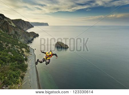 base-jumper prepears to jump from the cliff at sunrise in the mountains