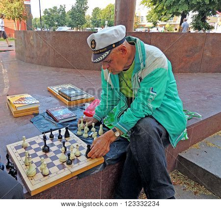 Voronezh, Russia - July 17, 2015: Mature men chess player with a cigarette in his mouth makes a move on the chess board in the city public garden. July 17, 2015 in Voronezh, Russia