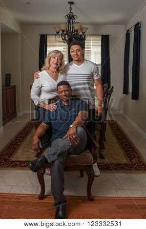 Wide view of handsome father seated with his multi-racial family.