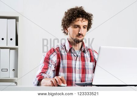 Young man in checked shirt typing on his notebook