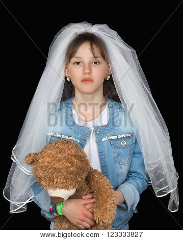 Girl teenager in a denim jacket with a toy and a veil. Concept - early marriage, marriage to minors