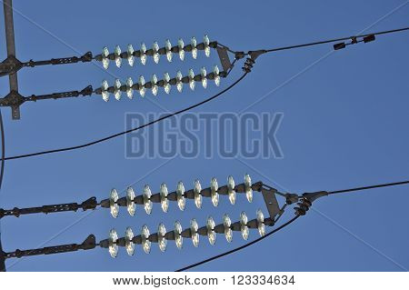 Insulators of power lines. Photo of power lines against the blue sky.