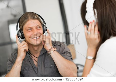 Portrait of young man and woman in office wearing headphones