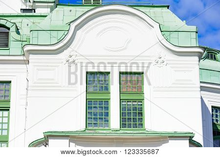 Kristianstad Sweden - March 20 2016: Architectural detail of the Theater in town. This is a window at the backside of the building. Green copper patina on the roof.