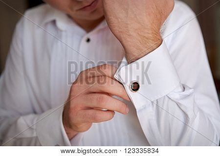 close up of a hand man how wears white shirt and cufflink.