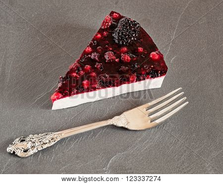 Slice of forest fruit panna cotta cake with silver fork on a textured gray granite slate.