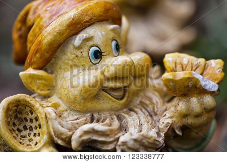 Garden gnome - detail of the head of the dwarf and a butterfly on his hand standing on the grass in the garden amid the flowers