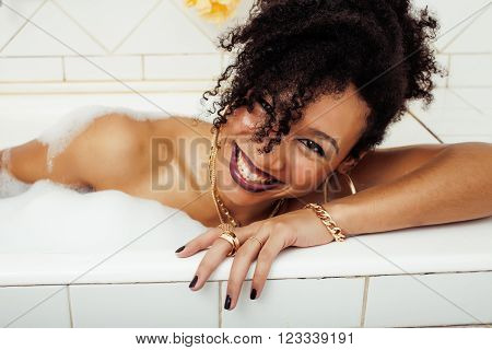 young beauty real afro-american teen girl laying in bath with foam, wearing swag jewelry