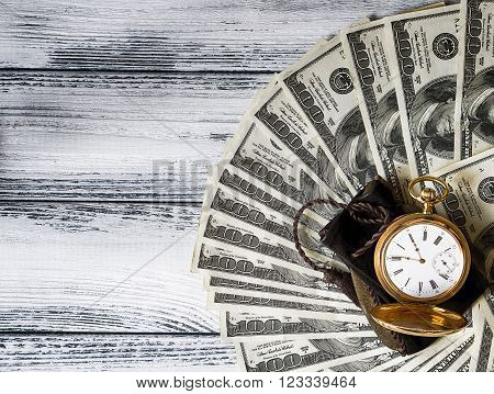 Stack Of Money Dollars Laid Out Like A Fan With Antique Gold Watch On White Retro Stylized Wood Back