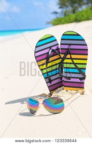 Multicolored flip-flops and sunglasses on a sunny beach. Tropical beach vacation and travel concept vertical compopsition