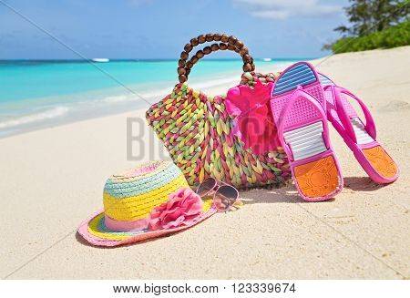Bag hat flip-flops and sunglasses on sunny beach tropical beach vacation and travel concept