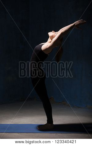 Beautiful sporty fit young woman in black sportswear working out indoors against grunge dark blue wall. Model doing Ardha Chakrasana Standing Backward Bend Pose. Full length