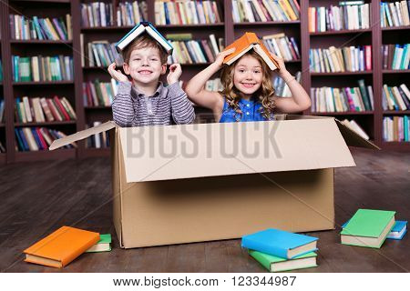 Playful childhood. Little children having fun with cardboard box. Children with books on heads. Children playing at room with bookshelf