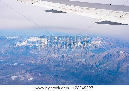 Aerial view of the Alps, Ecrins National Park, France, shot from aeroplane. High altitude mountain range and glaciers. Expansive view.