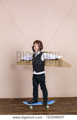 Little boy wearing school uniform and pilot hat. Boy is happy and smiling. Boy riding on skateboard