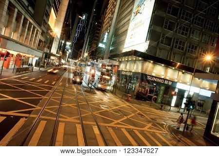 HONG KONG, CHINA - FEB 10: Night city streets with people standing on crossroad with urban structures on February 10, 2016. Hong Kong dollar is the eighth most traded currency in the world.