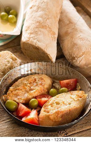Crusty homemade Italian ciabatta bread (toasts) on the wooden table