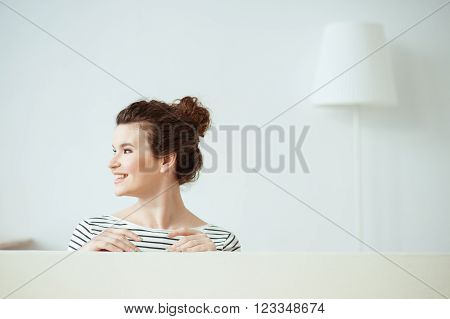 Cheerful young woman is making fun at home. She is standing behind the back of sofa in her apartment. The lady is looking aside and laughing