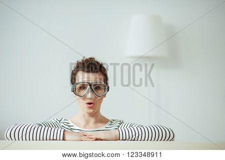 I am diving into the work completely. Portrait of young girl wearing a mask. She is looking at the camera with shock. The lady is leaning her arms on the back of sofa at home ** Note: Soft Focus at 100%, best at smaller sizes