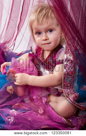 Little young east girl, sultana, Princess in Indian dress sari burqa scarf veil holding a pearl necklace sitting on a floor pillow at home interior under pink canopy. Childhood, copy space, doll house