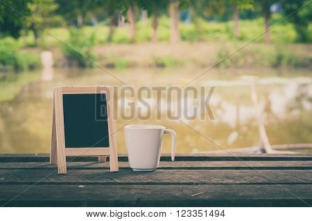 Small A-frame blackboard with blank area for text or message and coffee cup on rustic wood table in morning time with vintage filter effect
