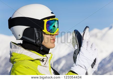 Close portrait of woman in ski mask and helmet standing over the mountains