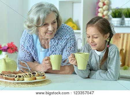 happy Senior woman with granddaughter with tea at home