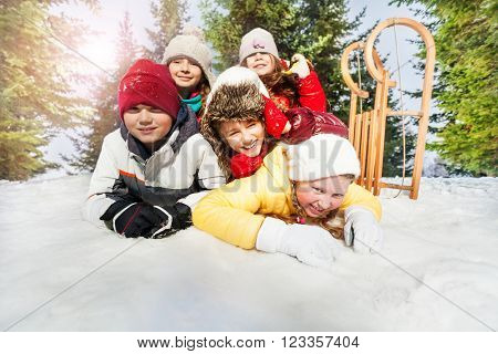 Close up picture of large group of diversity looking laughing kids laying on the snow at the winter forest