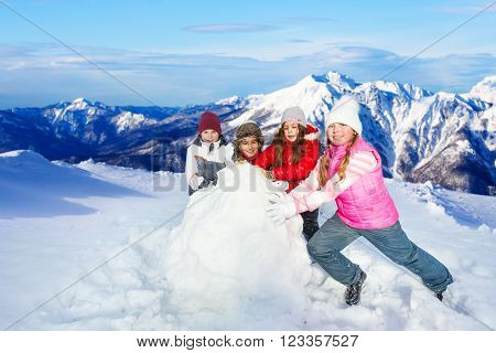 Four happy friends rolling up big snowball against beautiful snow mountains peaks