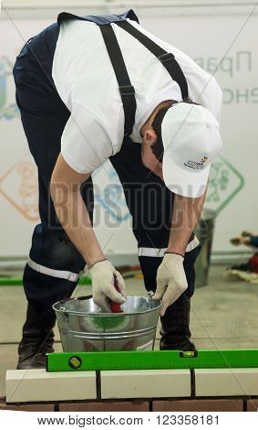 Tyumen, Russia - March 23. 2016: Open championship of professional skill among youth. World skills Russia Tyumen - 2016. Young bricklayer performs a task of competition of professionals