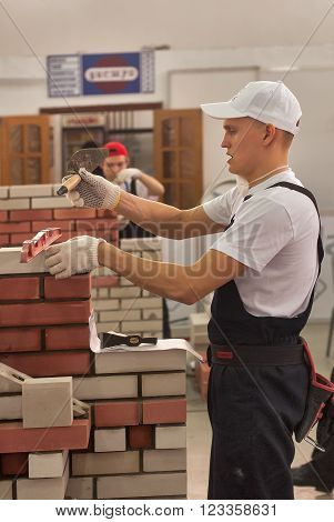 Tyumen, Russia - March 24, 2016: Open championship of professional skill among youth. World skills Russia Tyumen - 2016. Young bricklayer performs a task of competition of professionals