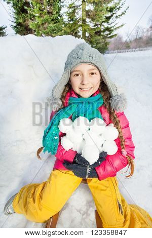 Close-up photo of smiling girl in colorful winter clothes holding snowballs near the snow fortress
