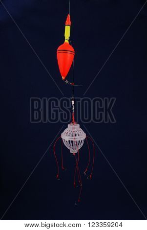 Fishing supplies: float, a feeding trough, hooks in a black background
