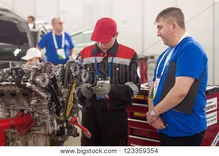 Tyumen, Russia - March 24. 2016: Open championship of professional skill among youth. World skills Russia Tyumen - 2016. Young car mechanic passes competition stage. Engine repair
