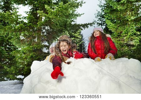 An adorable girl throwing snowballs in her winter wear playing with friends at the forest
