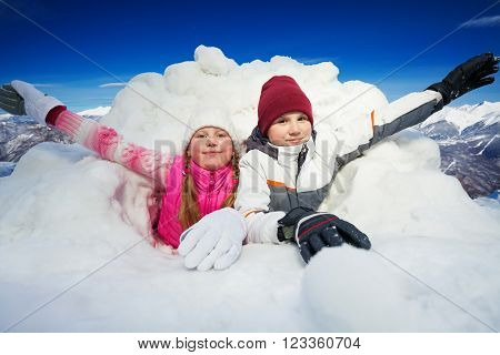 Two happy children flourishing their arms at snow cave outside in winter time