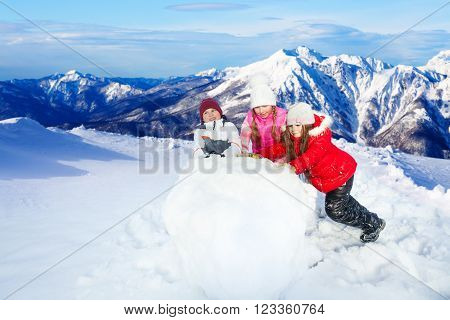 Three kids balling up the huge snowball making a snowman on top of beautiful mountain