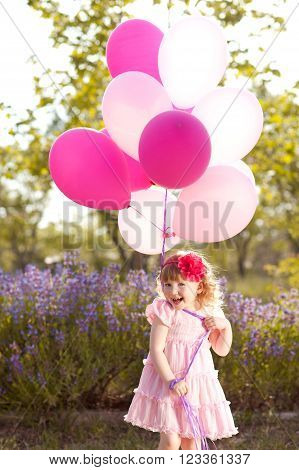 Kid girl 3-4 year old playing with air balloons outdoors. Wearing stylish pink dress. Childhood. Summer time.