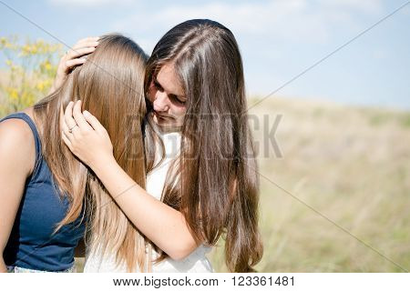 one comforts and expressing feelings of compassion for another: Two teenage girls,  beautiful young women girl friends having difficult times on the summer outdoors background closeup portrait