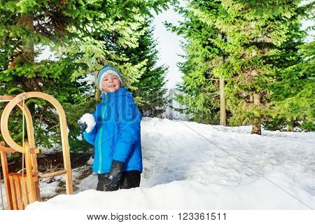 Little boy behind the snow wall throw snowball and smile