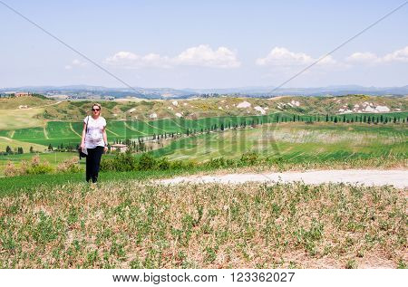 woman tourist strolling through Crete Senesi during summer holidays in Italy