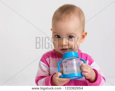 Adorable baby girl posing with a feeding-bottle filled with water