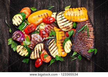 Beef steak and Grilled vegetables. On cutting dark board background.
