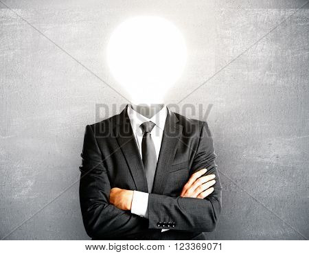 Idea concept with lamp headed businessman on light concrete wall background