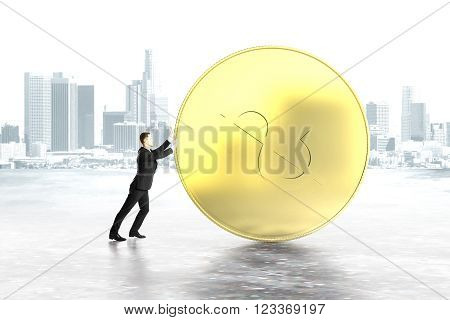 Businessman pushing huge dollar coin on grey city background